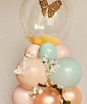 Bubble transparent balloon sitting on a cluster of 10 balloons decorated with flowers and butterfly