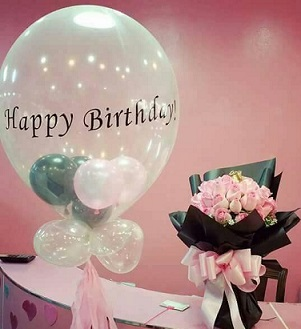 Happy Birthday printed hot air balloon with balloons stuffed inside and on the the stick accompanied with a 20 light pink roses bouquet