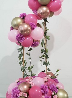 Cluster of Pink and gold balloons with pink flowers stuffed in between the balloons on 2 sticks and tied to a basket with pink and gold balloons similar as on top