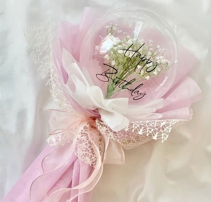Pink and White net wrapped a bubble balloon with print happy birthday message and gypsophillia inside the balloon