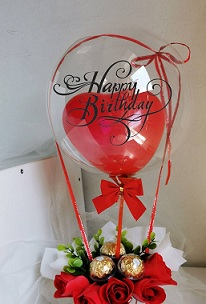 Red heart balloon stuffed inside a clear balloon tied with red riboons to a basket of 3 Ferrero and 3 red roses