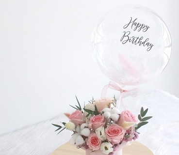 Happy birthday print on the transparent balloon with 12 white and light baby pink roses basket attched with pink ribbons
