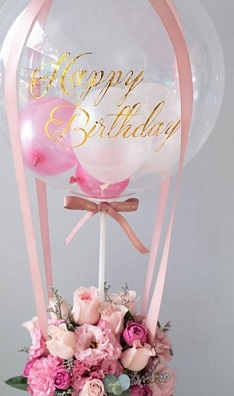 Pink balloons inside a clear bubble with pink ribbons and 12 pink roses and carnations