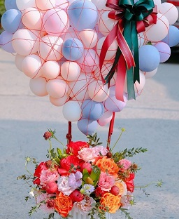 Pink and blue balloons with big ribbon bows 25 in number on the sticks of a basket filled with orange and red flowers
