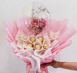Transparent Balloon with print message happy Birthday and stuffed with small flowers tied on the outside are 16 Ferrero rocher chocolates wrapped in pink and white