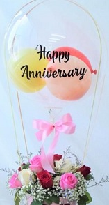 Happy anniversary print on the transparent balloon stuffed with small balloons and 12 pink red and white in a box wrapped with pink ribbons