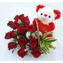 Teddy sitting in a basket of 12 red roses