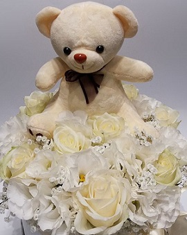 Brown 6 inches Teddy bear with a basket of 20 white roses and white gerberas