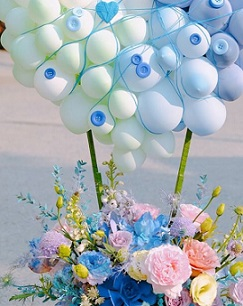 25 Blue Balloons cluster on top held with sticks on a basket of pink blue and yellow roses flowers
