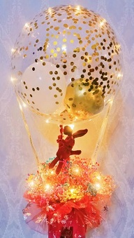 Golden confetti inside the transparent balloon tied to a box with 8 ferrero rocher chocolates in red net with string lights