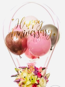 Happy anniversary print on the transparent balloon stuffed with small pink red and gold balloons with 6 White lilies flowers in a box with pink ribbons