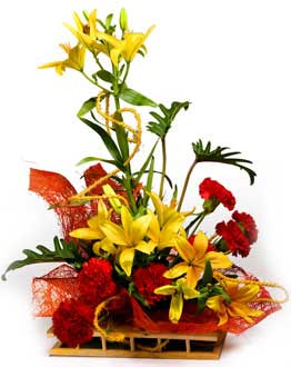 Yellow liliums red carnations basket