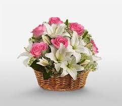 White lilies pink roses in a basket