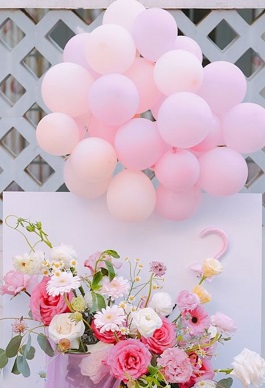 20 Pink Balloons on sticks tied with a basket with pink and white roses