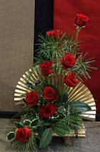 8 Red Roses with Golden fan and round palm leaves in Basket