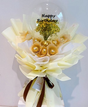 Transparent Balloon with print message happy Birthday and stuffed with small flowers tied on the outside are 16 Ferrero rocher chocolates wrapped in cream and white