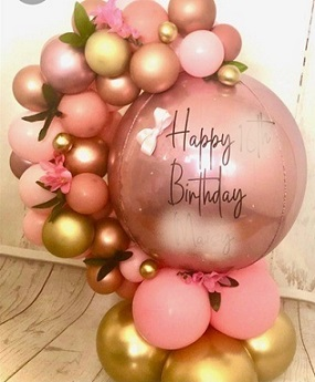 Happy birthday print on the transparent balloon with a garland of 30 pink and golden small balloons wrapped around it and decorated with 12 white flowers