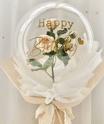 A bouquet of single clear balloon with happy birthday printed wrapped in white and jute with white rose inside