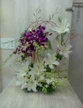 Purple Orchids and White Lilies climbing on handle from either side of Basket