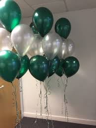 20 green and silver gas inflated balloons tied with ribbons