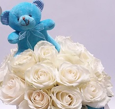 Blue 6 inches Teddy bear in a basket of 15 white roses