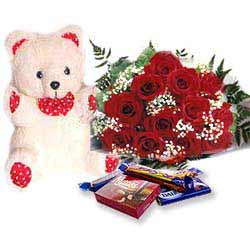 A teddy, a velvet heart, chocolates and a single rose in a basket.
